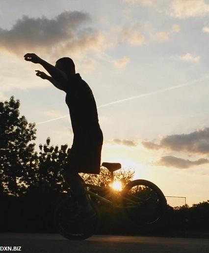 BMX Flatland riding at sunrise: no hand hang ten trick